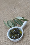 Saucer with olives on a burlap Royalty Free Stock Images