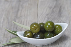 Saucer with olives on a wooden surface royalty free stock images