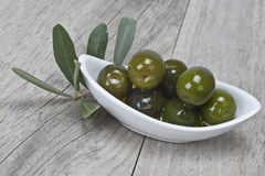 Saucer with olives on a wooden surface stock image