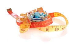 Saucer with pills and measuring tape. Transparent saucer with pills and measuring tape Royalty Free Stock Image