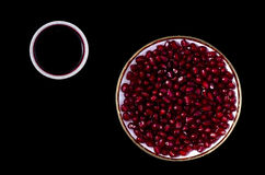 Saucer with pomegranate seeds and cup of juice. On a black background Royalty Free Stock Images
