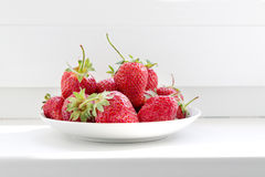 Saucer with strawberries. On the windowsill Stock Photo