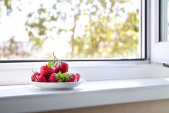 Saucer with strawberries. On the windowsill Royalty Free Stock Photo