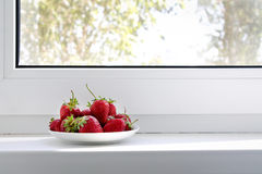Saucer with strawberries. On the windowsill Royalty Free Stock Image