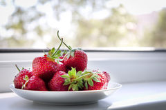 Saucer with strawberries. On the windowsill Stock Images