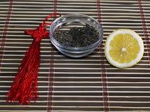 Saucer with tea and a row a lemon, on a rug Stock Photos