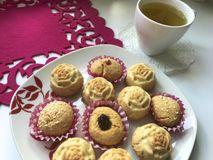 On the saucer there are cupcakes, in paper form for baking. There is a cup of tea nearby. On the saucer there are cupcakes, in paper form for baking. There is a Stock Image