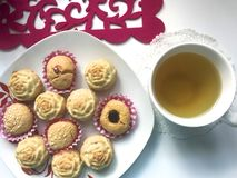 On the saucer there are cupcakes, in paper form for baking. There is a cup of tea nearby. On the saucer there are cupcakes, in paper form for baking. There is a Stock Photos