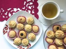 On the saucer there are cupcakes, in paper form for baking. There is a cup of tea nearby. On the saucer there are cupcakes, in paper form for baking. There is a Royalty Free Stock Images