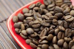 Saucer und Kaffeebohnen auf einer Bambusmatte Stockbild