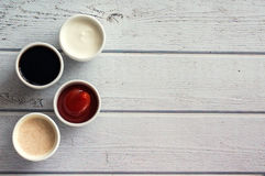 Sauces кетчуп, мустард, майонез, сметана, соевый соус в шарах глины на деревянной белой предпосылке Стоковые Фото
