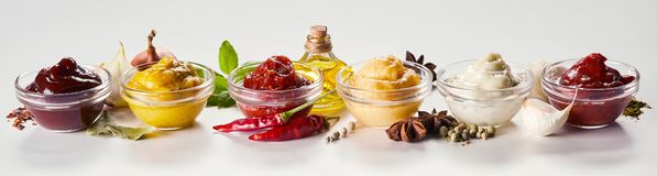 Sauces, dressings and marinades with ingredients. Row of glass bowls with sauces, dressings and marinades with ingredients including aromatic spices, herbs and royalty free stock image