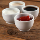 Sauces ketchup, mustard, mayonnaise, sour cream, soy sauce in clay bowls on wooden background Stock Photography