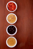 Sauces ketchup, mustard, mayonnaise, sour cream, soy sauce in clay bowls on wooden background. Top view Royalty Free Stock Photography