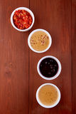 Sauces ketchup, mustard, mayonnaise, sour cream, soy sauce in clay bowls on wooden background. Top view Stock Image
