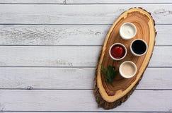Sauces Ketschup, Senf, Majonäse, Sauerrahm, Sojasoße in den Lehmschüsseln auf hölzernem weißem Hintergrund Stockbild