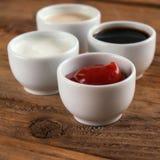 Sauces la salsa de tomate, mostaza, mayonesa, crema agria, salsa de soja en cuencos de la arcilla en fondo de madera Fotografía de archivo