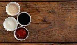 Sauces la salsa de tomate, mostaza, mayonesa, crema agria, salsa de soja en cuencos de la arcilla en fondo de madera Fotos de archivo