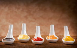 Sauces mixed in the ceramic spoons. On wooden table Royalty Free Stock Photos