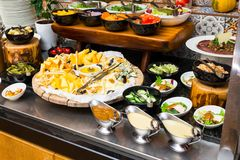 Sauces in sauceboats for a buffet table. Sauces in sauceboats near salads and sliced cheese on a plate for guests of a buffet table stock image