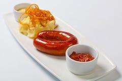 Saucisse avec les pommes de terre et la choucroute d'un plat blanc image stock