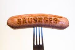 Saucisse avec une inscription goupillée sur une fourchette, sur un fond blanc Photos stock