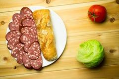 Saucisse coupée en tranches d'un plat blanc avec du pain sur un backgroun en bois Photo libre de droits