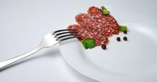 Saucisse coupée en tranches d'un plat blanc avec une fourchette décorée des pois doux et du persil images stock