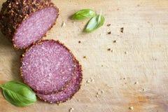 Saucisse coupée en tranches de salami avec le basilic Images libres de droits