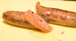 Saucisse coupée en tranches sur le fond jaune Photographie stock libre de droits