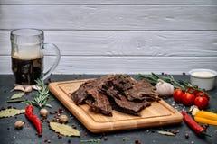 Saucisse délicieuse et fumée sur un conseil foncé avec de la bière et épices Casse-croûte savoureux fait main des ingrédients nat images libres de droits