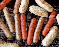 Saucisse de francfort et saucisse grillées sur le barbecue au-dessus des charbons Photos stock
