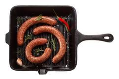 Saucisse faite maison crue pour griller dans la casserole D'isolement sur le blanc Image stock