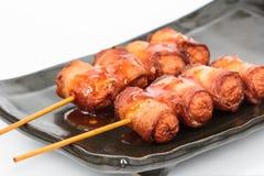 Saucisse frite roulée avec le lard image stock