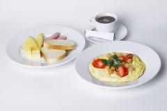 Saucisse, fromage, pain blanc, beurre, céréale, pot, café, oeufs brouillés figés de petit déjeuner avec des tomates Image stock