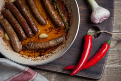 Saucisse grillée d'agneau avec le romarin et l'ail dans une poêle en huile d'olive images libres de droits