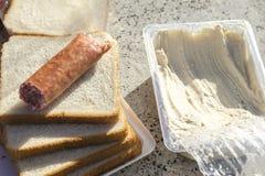 Saucisse, pain, houmous sur la plage Voyageurs de budget de nourriture Le concept du casse-croûte bon marché Athènes, Grèce photographie stock