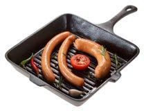 Saucisse pour griller dans la casserole D'isolement sur le blanc Images libres de droits