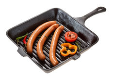 Saucisse pour griller dans la casserole D'isolement sur le blanc Image stock