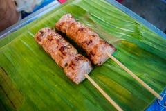 Saucisse thaïlandaise avec la vente de bâton sur la feuille de banane au marché en plein air Photos stock