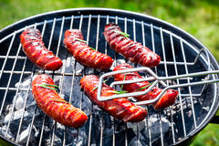 Saucisses épicées avec les épices et le romarin sur un gril Photo libre de droits
