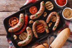 Saucisses avec des légumes sur un plan rapproché de gril vue supérieure horizontale image libre de droits