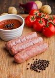 Saucisses crues de boeuf avec les tomates et le sause à bord Photos libres de droits