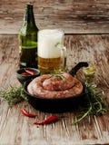 Saucisses crues de boeuf sur une casserole de fonte, foyer sélectif Image stock