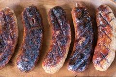 Saucisses délicieuses de viande grillées sur un fond en bois de plat image stock