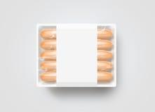 Saucisses dans la maquette jetable en plastique blanche vide de boîte, d'isolement, Images libres de droits