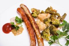 Saucisses de Fried Munich avec des légumes et des sauces Image libre de droits