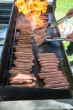 Saucisses de gril de flamme sur un barbecue photo libre de droits