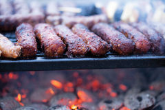 Saucisses de porc et de boeuf faisant cuire au-dessus des charbons chauds sur un barbecue Image libre de droits