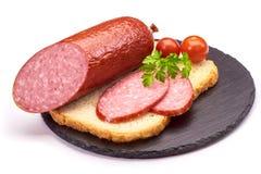 Saucisses de salami coupées en tranches avec le poivre, l'ail et le romarin sur la planche à découper sur la table en bois Photo stock